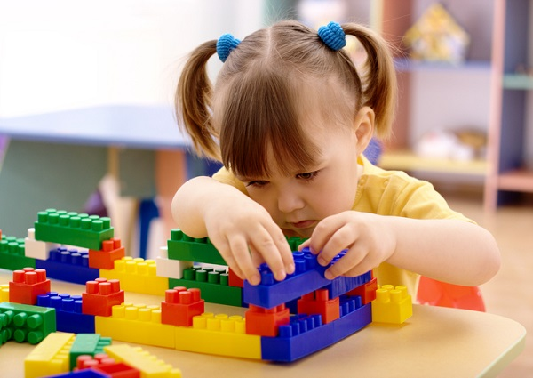 Little girl with pig tails playing with Legos at her seat